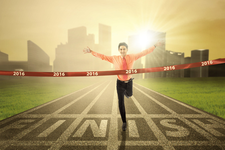 winner: Successful businessman winning the race competition and crossing the finish line with numbers 2016