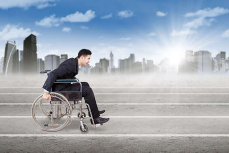 handicap: Image of male worker with format suit and sitting on the wheelchair, pushing the wheelchair on the race line