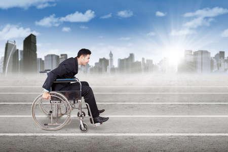 silla de ruedas: Imagen de trabajador masculino con traje formato y sentado en la silla de ruedas, empujando la silla de ruedas en la línea raza