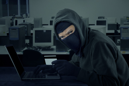 web scam: Image of male robber wearing mask and staring at the camera while stealing credit card information in the office