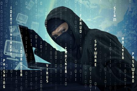 virus informatico: Imagen de hacker masculino llevaba pasamontañas, que roba el ordenador portátil y la identidad del usuario