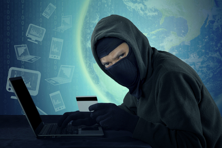 villain: Male villain wearing mask and staring at the camera while stealing credit card identity with notebook computer