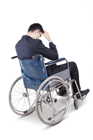 depressed person: Image of depressed young businessman with formal suit, sitting on the wheelchair, isolated on white background