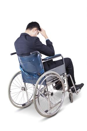 persona deprimida: Imagen de joven hombre de negocios deprimido con traje formal, sentado en la silla de ruedas, aislado en fondo blanco