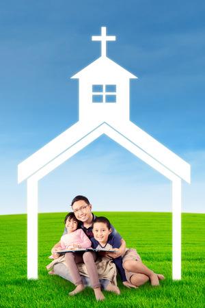 familia cristiana: Retrato de joven padre y sus niños que se sientan en el campo durante la lectura de libro bajo el símbolo de la iglesia