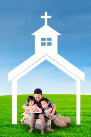 church people: Image of young father teaching his children to read a book on the meadow under church symbol Stock Photo