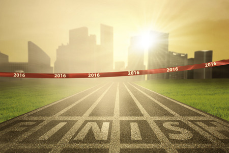 tape line: Image of an empty finish line with numbers 2016 on the tape and bright sun rays at the end of track Stock Photo