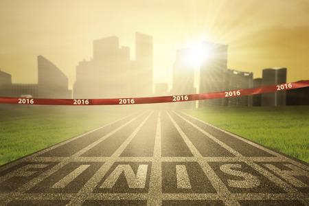 pista de atletismo: Imagen de una l�nea de meta vac�a con los n�meros de 2016 en la cinta y los rayos del sol brillante en el extremo de la pista Foto de archivo