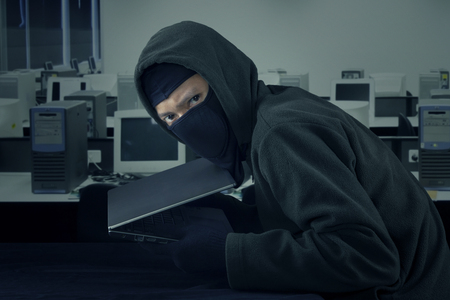 villain: Image of male villain stealing laptop computer in the office while wearing mask and staring at the camera