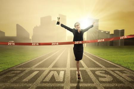Foto van jonge zakenvrouw winnen van de race concurrentie en het overschrijden van de finish terwijl het dragen van een trofee