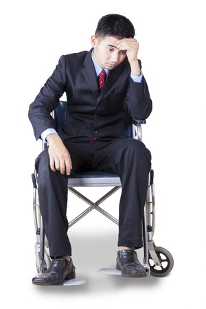 stressful: Portrait of young businessman wearing formal suit, sitting on the wheelchair and looks stressful Stock Photo