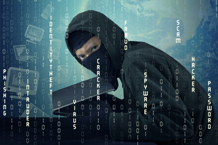 web scam: Image of male thief with binary code background, wearing mask and stealing laptop computer Stock Photo