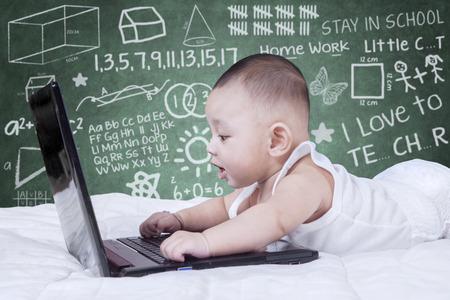 circulo de personas: Imagen del bebé de sexo masculino lindo que usa el ordenador portátil en la cama con fondo garabatos en la pizarra