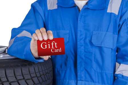 mechanist: Mechanic person with blue uniform lean on tires and show a gift card