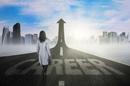 zakelijk: Foto van jonge zakenvrouw lopen op de straat met opwaartse pijl en carrière tekst Stockfoto
