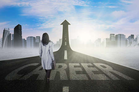 career: Photo of young businesswoman walking on the street with upward arrow and career text