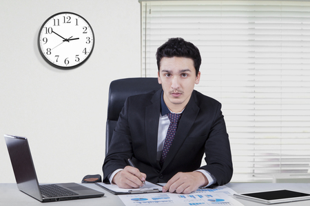 overwork: Image of young caucasian businessman working in the office with a clock on the wall and laptop on the table