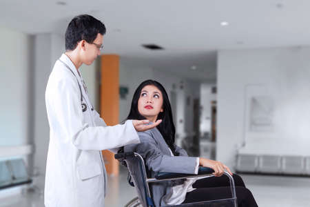 handicapped person: Image of beautiful disabled woman sitting on the wheelchair while talking with a doctor in the hospital corridor