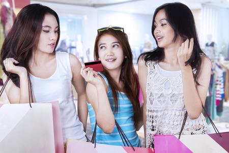 chicas de compras: Imagen de tres adolescentes que sostienen una tarjeta de crédito, mientras que con bolsas de compras en el centro comercial
