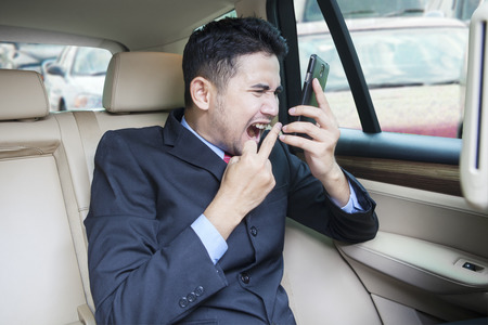 businessman phone: Image of young businessman sitting in the car and looks angry on the phone