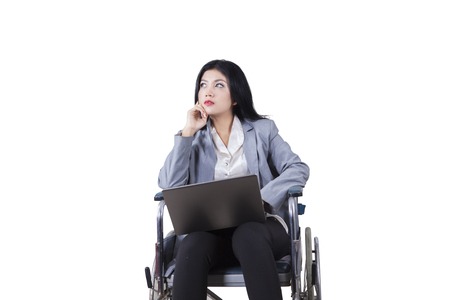 daydreaming: Photo of disabled businesswoman daydreaming on the wheelchair while holding laptop computer, isolated on white