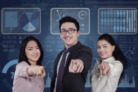 hand pointing: Three members of successful businesspeople pointing at camera in front of modern futuristic screen