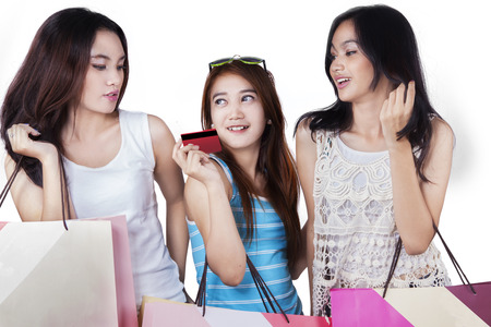 shopping card: Portrait of three beautiful teenage girls holding shopping bags and credit card in the studio Stock Photo