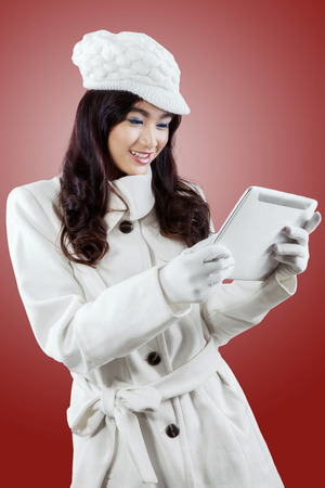 using tablet: Beautiful young girl enjoy winter holiday and using a digital tablet while wearing winter coat
