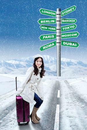 valise voyage: Jeune fille assise sur les bagages à la rue avec panneau de choix de destination pour les vacances d'hiver