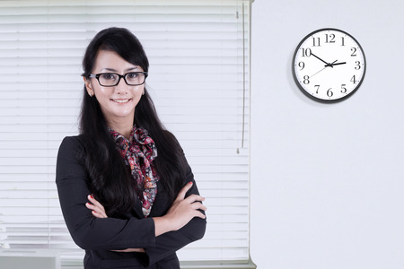 office wall: Photo of confident businesswoman standing in the office and smiling at the camera with clock on the wall Stock Photo