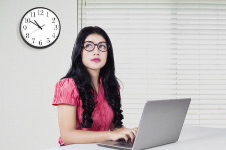 watch over: Photo of young asian woman working in the office with notebook computer and a clock on the wall
