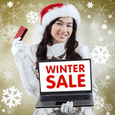 capelli lunghi: Adolescente attraente lo shopping online utilizzando una carta di credito e un computer portatile con uno sfondo di Natale