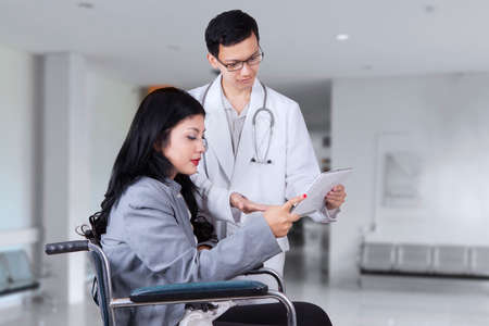 informe: Imagen del doctor de sexo masculino que usa la tableta digital para mostrar informe m�dico al paciente discapacitado, dispar� en el hospital