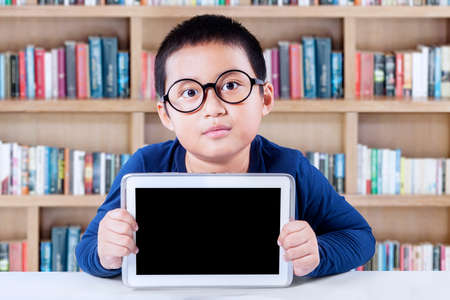 internet school: Portrait of little boy wearing glasses and sitting in the library while holding empty tablet screen