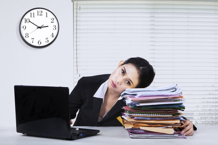 watch over: Image of young female businesswoman looks tired, working overtime with laptop and paperworks Stock Photo