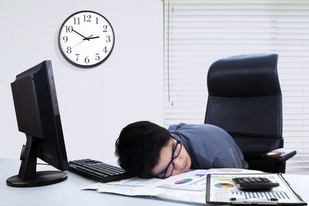 watch over: Image of young businessman sleeping on the table with financial graph and computer on the desk