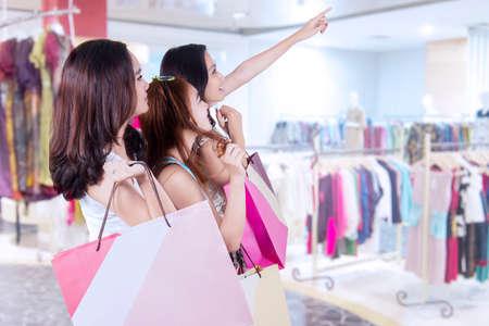centro comercial: Imagen de tres atractiva adolescente de pie en el centro comercial en el ejercicio de bolsas de la compra y apuntando a una tienda Foto de archivo