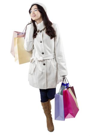 botas de navidad: Muchacha del encanto con abrigo de invierno y llevar bolsas de la compra, aisladas sobre fondo blanco