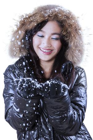 bata blanca: Muchacha asiática joven que llevaba ropa de invierno celebración de nieve con sus manos, aislado más de blanco Foto de archivo