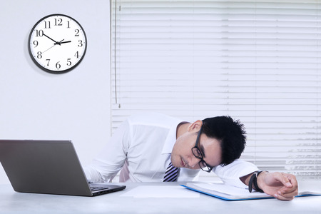 watch over: Photo of young businessman sleeping on the desk with a clock on the wall, shot in the office Stock Photo