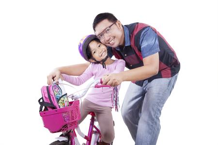 niños en bicicleta: Niña alegre sonriendo a la cámara mientras se conduce una bicicleta con su padre en el estudio, aislado en blanco