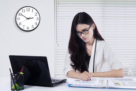 laptop computer: Image of young businesswoman working in the office with laptop computer and financial graph on the table Stock Photo