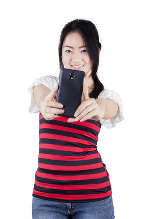 japanese people: Portrait of beautiful chinese girl using mobile phone to take selfie photo in the studio