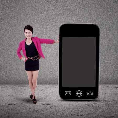 businesswoman standing: Businesswoman standing next to smartphone on grey background