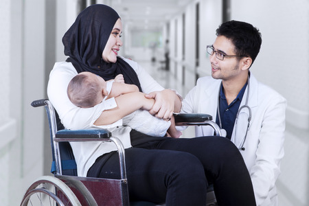 asian baby: Portrait of male doctor talking with young mother sitting on the wheelchair, shot in the hospital Stock Photo