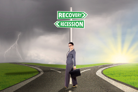 road to recovery: Young businesswoman standing on the road with signpost directing to recession or recovery financial Stock Photo
