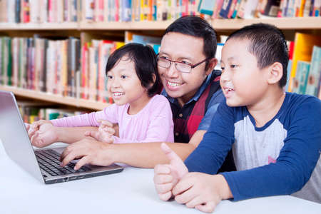 asian adult: Portrait of two elementary school student using laptop for studying with their teacher in the library Stock Photo
