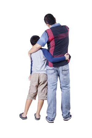 젊은 아버지와 서로 포용 아들의 후면보기 스튜디오에서 복사본 공간을 찾고있는 동안