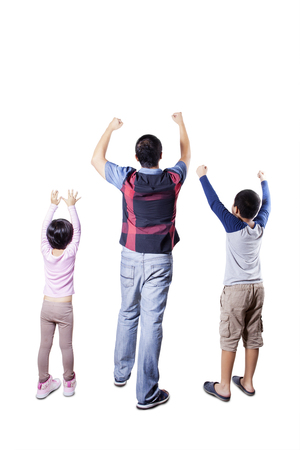 Rear view of happy young father and his children standing in the studio and raise hands together Standard-Bild