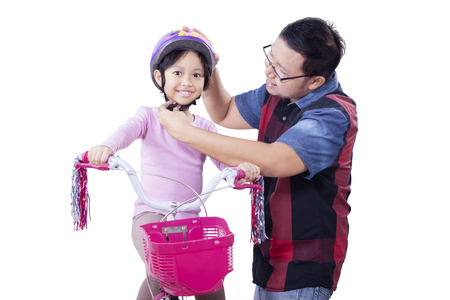 a helmet: Portrait of young father fasten helmet on the daughters head before ride a bike, isolated on white background Stock Photo